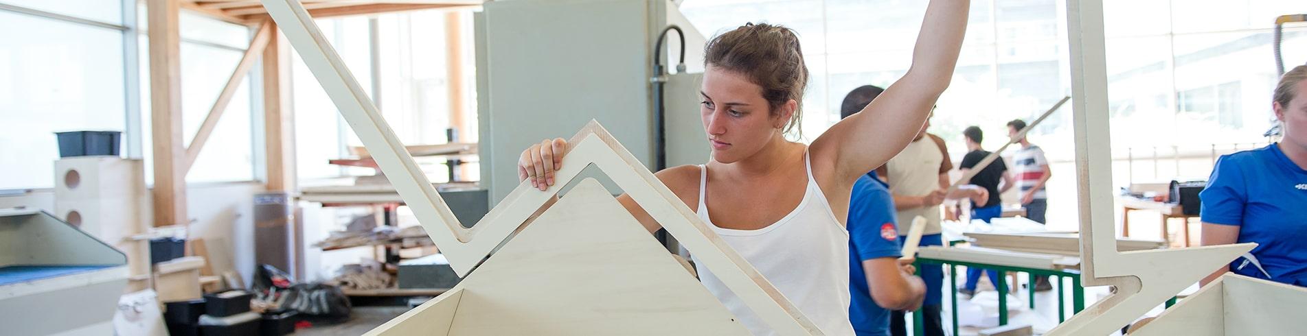 étudiante qui monte une structure en bois