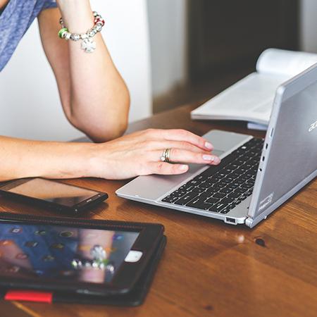 main de femme tapant sur un ordinateur portable